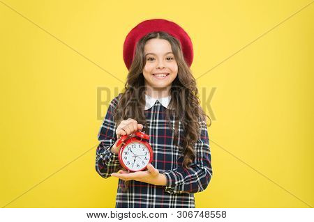Clock Is Ticking. Small Child Smiling With Mechanical Clock On Yellow Background. Adorable Kid With