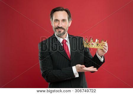 Rich Reward. Mature Businessman Showing Crown Reward On Red Background. Successfil Big Boss Awarding