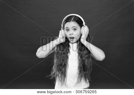 Music plays an important part lives teenagers. Powerful effect music teenagers their emotions, perception of world. Girl listen music headphones on red background. Modern gadget concept. Music taste. poster