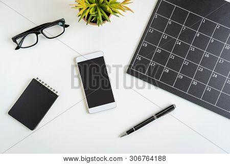 Planning Calendar With Smartphone On Business Desk Office, Top View