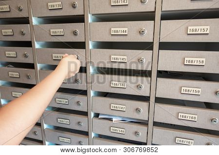 Close-Up of Woman Hand Insert a Key to Unlock Mailbox Locker in Apartment, Interior Mail Letterbox Cabinet in Condominium. Row of Post Locker in Residential Building.