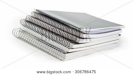 Stack Of The Different Exercise Books With Wire Spiral Binding At Selective Focus On A White Backgro