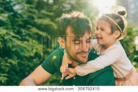 Outdoor Image Of Happy Cute Little Girl Smiling And Playing With Her Father. Handsome Dad And Pretty