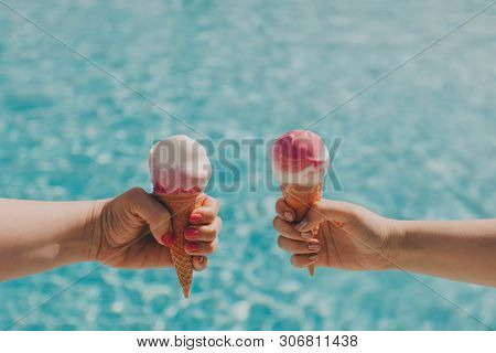 Two Friends Hold Pink Ice Cream On A Hot Day On Background Of A Blue Pool. Hands With A Beautiful Ma