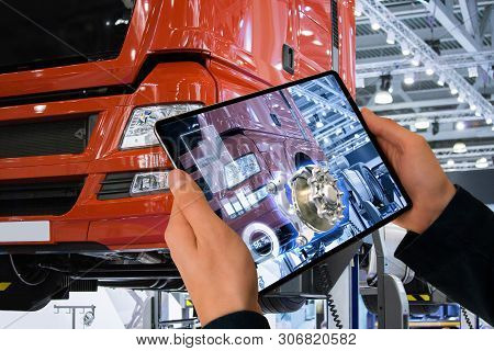 Serviceman Repairing A Truck Using Augmented Reality Application.