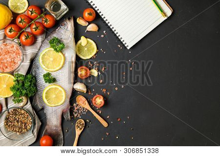 Fresh Fish Seabass And Ingredients For Cooking With Blank Notebook For Text Menu. Raw Fish Seabass W