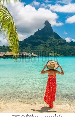 Bora Bora Tahiti exotic tropical vacation destination tourist woman on ocean beach at view of Mt Otemanu in French Polynesia. Girl in red dress and hat relax on honeymoon getaway.