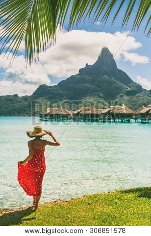 Tahiti resort travel honeymoon destination tourist woman walking on beach of private island at overwater bungalows villas hotels in Bora Bora, French Polynesia. Luxury hotel vacation.