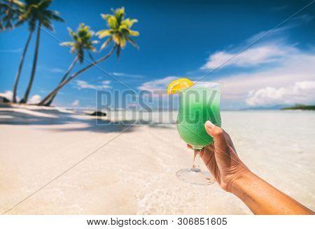 Blue Hawaiian drink cocktail woman drinking curacao liqueur on beach vacation travel in Caribbean destination. Summer fun lifestyle.