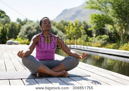 Mature african woman practicing yoga and meditates near swimming pool outdoor. Fitness black lady sitting in lotus pose with closed eyes. African american woman meditating at poolside with copy space.