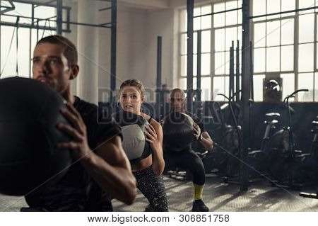 Group of three people doing squats while holding heavy medecine balls. Young men and fitness woman doing bodyweight exercises using weight ball. People in a row squatting with weighted balls at gym.