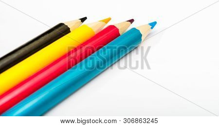 Four Colored Pencils. The Colors Cyan, Magenta, Yellow And Black. The Concept Of Polygraphy.