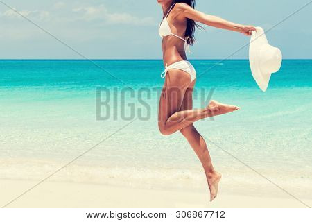 Happy beach swimsuit woman jumping of joy with sun hat on caribbean travel vacation winter holiday getaway. Tanned legs bikini girl sun tanning feeling good about her toned body. Sun protection
