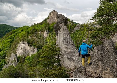 Hiker With Hiking Poles Looking At Sulov Rocks, Slovakia