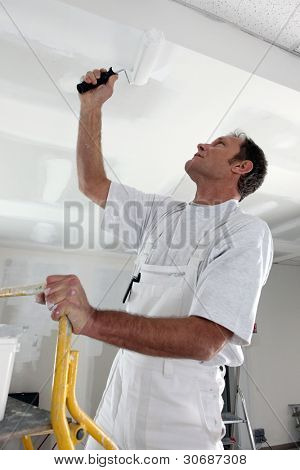 Man painting ceiling with roller poster