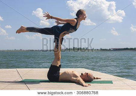 Acro Yoga Concept. Pair Yoga. Couple Of Young Sporty People Practicing Yoga Lesson With Partner, Man