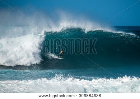 OAHU / USA - DECEMBER 05, 2019: Surfer rides giant wave at the famous Banzai Pipeline surf spot located on the North Shore of Oahu in Hawaii