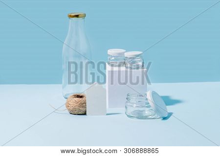 Composition Of Glass Jars On Pedestal, Empty Milk Bottle, Hank Of Twine And Blank Tag Over Blue Back