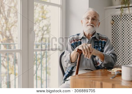 Positive Senior Grandfather With Grey Hair And Beard Sitting At Home