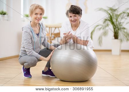 Smiling Physiotherapist With Elderly Woman Laying On Exercising Ball During Physical Therapy