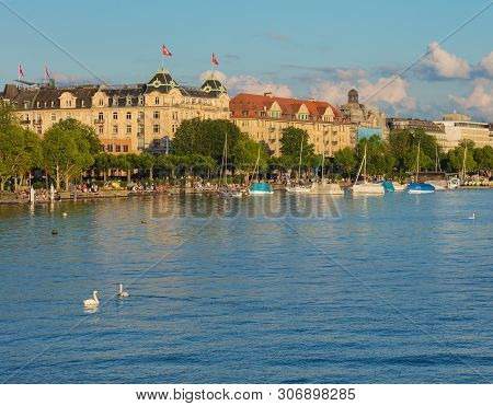 Zurich, Switzerland - June 16, 2019: Lake Zurich At Sunset, People On Its Embankment, Buildings Of T