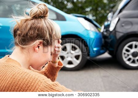 Female Motorist With Head In Hands Sitting Next To Vehicles Involved In Car Accident