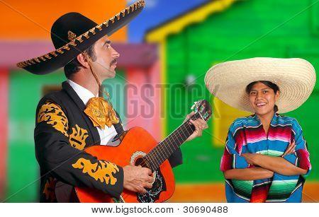 Mexican mariachi charro man singing a song to a poncho Mexico girl