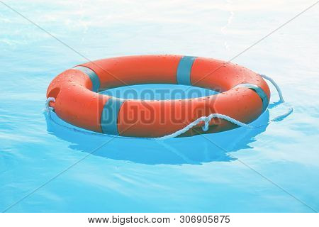 Orange Lifebuoy Pool Ring Float On Blue Water. Life Ring Floating On Top Of Sunny Blue Water. Life R