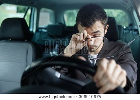 Sleepy Young Man Rubs His Eyes With His Right Hand. His Left Hand Is On The Steering Wheel. He Is Si