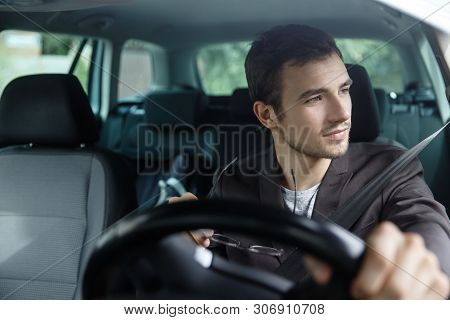Delighted Young Man Is Looking Trough The Window While Driving His Car. He Is Holding His Glasses At