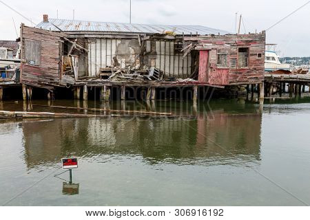 Derelict buildings on a pier in South Portland, Maine, Usa. A No Tresspassing marker is in the water to keep people away from these unsafe structures.