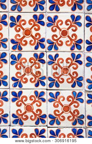 Vintage decorative Portugese style cermaic wall tiles, with floral design in orange and blue, over hite background.
