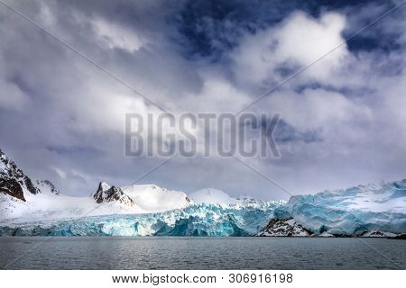 Mountains, snow and blue glacial iceof the Smeerenburg glacier, Svalbard, and archipelago between mainland Norway and the North Pole.