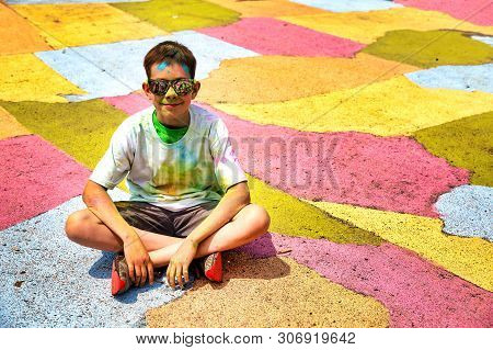 Boy After The Crazy Color Run Marathon Sitting On A Colorful Map. Copy Space For Your Text