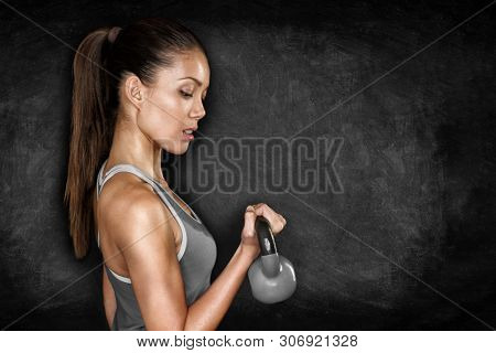 Fitness exercise woman lifting kettlebell weight doing strength training workout for biceps muscles. Gym Asian Caucasian female athlete sweating on black chalkboard texture background.