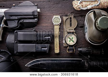 Military tactical equipment for the departure. Assortment of survival hiking gear on wooden backgrou