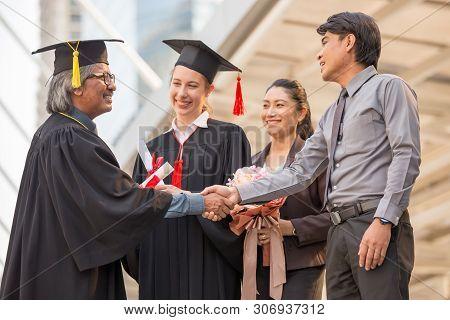 Business Man Handshaking With Senior Graduates On City Background.
