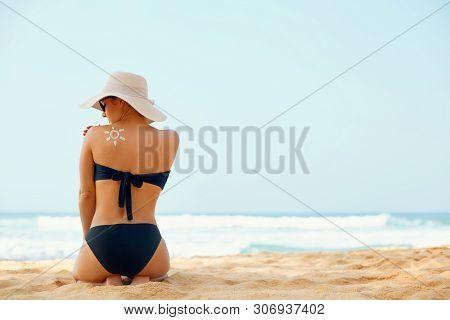 Beautiful Woman In Bikini Applying Sun Cream On Tanned  Shoulder. Sun Protection. Skin And Body Care