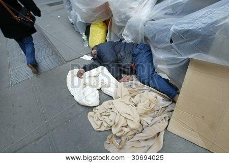 NEW YORK - FEBRUARY 12: A pedestrian walks past a homeless man sleeping on 33rd Street near 8th Avenue on February 12, 2005 in New York City.