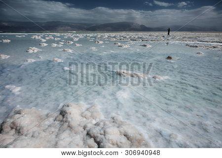 Silhouette of man walking on Dead Sea salt shore.