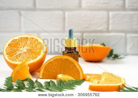 Vitamin C And Mesotherapy. Serum With Vitamin C In Brown Glass Bottles, Leaf Fern And Orange In A Cu