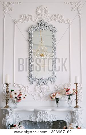 Fireplace And Mirror Over It In The Living Room Area Decorated With Plasterwork And Flowers