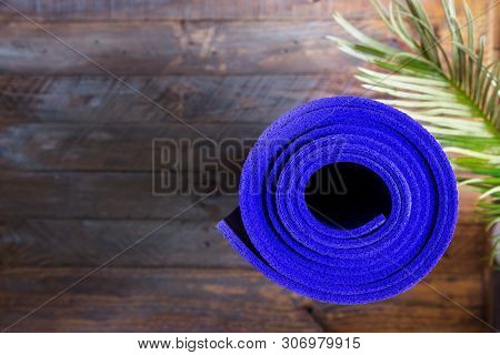 Blue Rolled Yoga Mat Lying On Wooden Background With Green Palm Leaf. Fitness Harmony Meditation Wor
