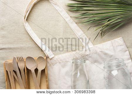 Cotton Fabric Tote Bag Wooden Flatware Cutlery Crystal Jar Bottle Green Palm Leaf On Linen Backgroun