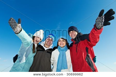 Group of happy young smiling people in warm clothing outwear at winter outdoors over blue sky