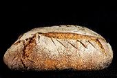 Loaf (or miche) of French sourdough, called as well as Pain de campagne, on display on a black background. Pain de Campagne is a typical French huge loaf of bread abiding by traditional codes poster