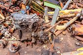 Aged internal combustion engine is placed among rusted parts of obsolete equipment in industrial complex. poster