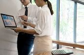 business businessman and woman stand in meeting analyses, on the table have chart graphy marketing plan in business project poster