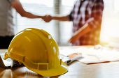construction worker team hands shaking greeting start up plan new project contract behind yellow safety helmet on workplace desk in office center at construction site, partnership, contractor concept poster