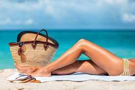 Suntan beach vacation woman legs lying on sand towel relaxing on summer holidays. Body care sexy toned leg for cellulite or hair removal laser treatment concept.